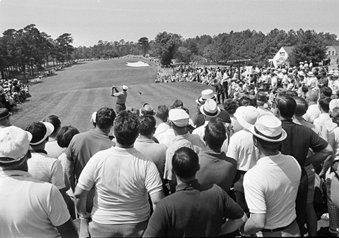 B&W photo circa mid-1960s showing gallery behind tee at PGA golf tournament watching a player tee off