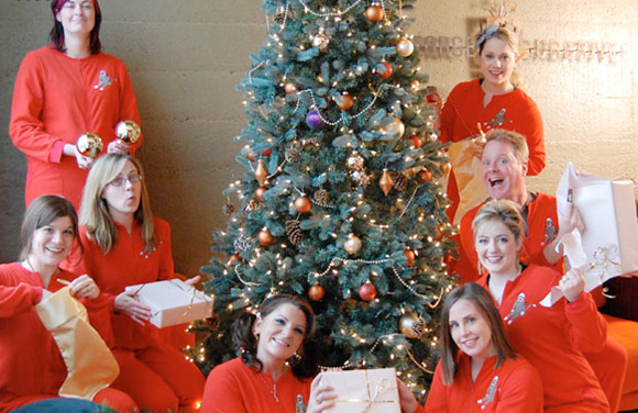 Employees at Rusty George Creative posing for Christmas card photo all wearing red pajamas or long underwear and opening gifts around a Christmas tree