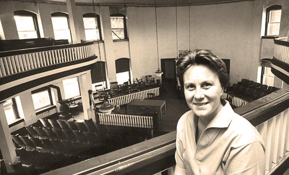 photo of To Kill A Mockingbird author Harper Lee sitting in balcony of Monroe County Courthouse in Monroeville, Alabama where her trial lawyer father had argued cases