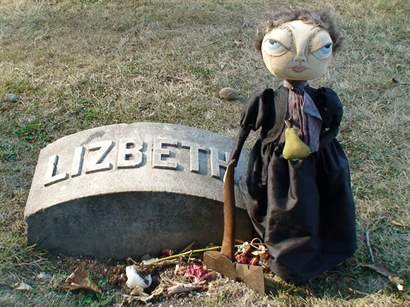 gag photo showing a little Lizzie Borden doll with an ax standing next to Lizzie Borden's grave in Fall River, Massachusetts
