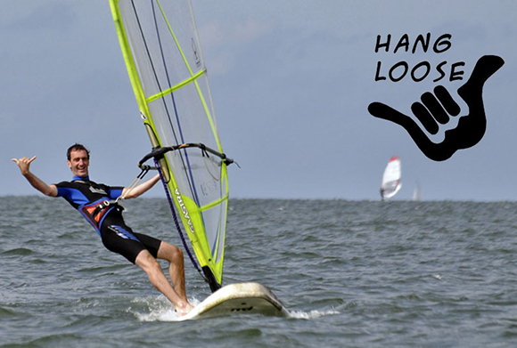 photo of man in wetsuit windsurfing and giving traditional Hawaiian hand signal for hang loose