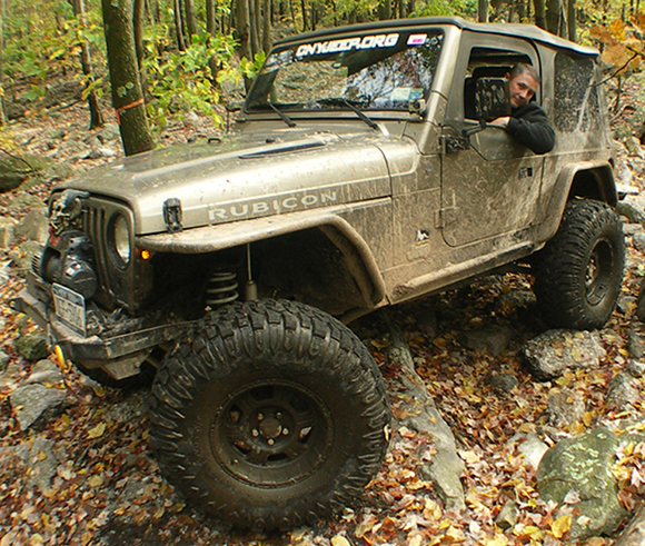 reference photo showing guy leaning out window of his mud-splattered jeep on rocky ground in forest