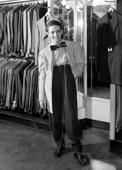 period photo of young teenage kid wearing zoot suit with wide shoulders, big bowtie, and long watch chain standing looking cool in men's clothing store