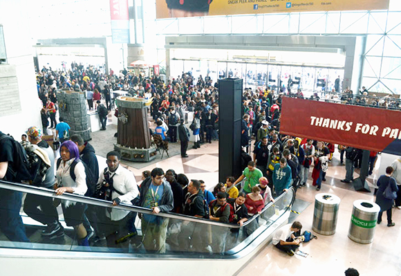 big crowd of people arriving for and riding elevators to 2012 New York Comic Con comics and pop culture convention