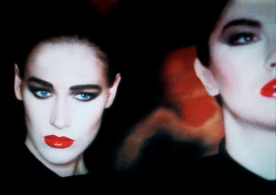 Still photo from Robert Palmer Addicted To Love video showing girl with white face, dark eye mascara and makeup, and very red lips
