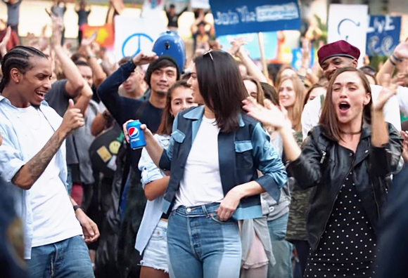 Kendall Jenner with Pepsi soda can getting thumbs-up applause enthusiastic reception from generic happy politically correct diverse crowd protestors