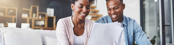 stock photo young black couple sitting on couch living room laughing looking at sheaf papers