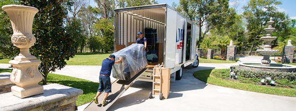 header image two guys moving desk into moving van American Van Lines post about moving myths