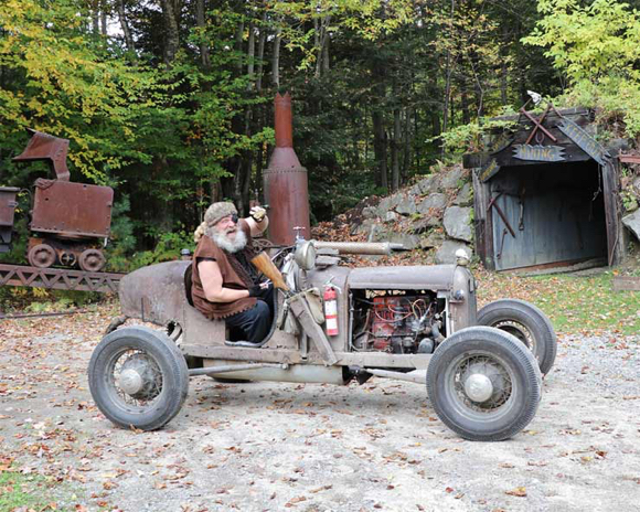 The Wolfman in junky rusty old car made spare parts telling train passengers to get off his land at Clark's Bears amusement park roadside attraction Lincoln NH