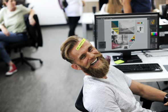 laughing guy with blond hair beard at computer with post-it note on his forehead which says Be Happy