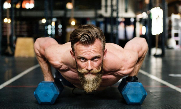 stock photo guy with blond beard working out at gym with weights doing pushups