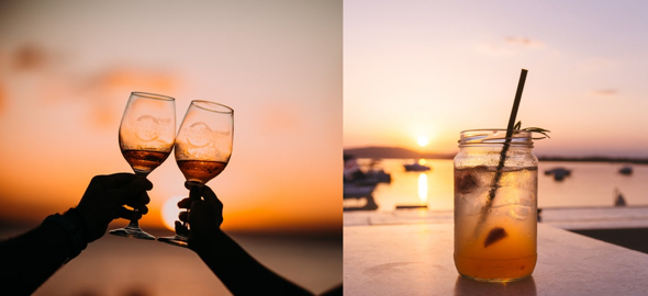 hands holding glasses toasting each other at sunset on beach drink in Mason jar on table with harbor at sunset in background